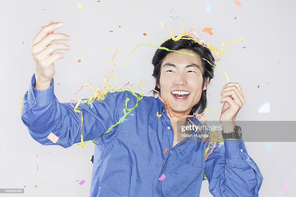 Portrait of young man with confetti : Stock Photo