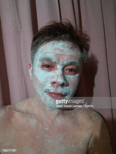 Portrait Of Young Man With Face Mask Against Curtain