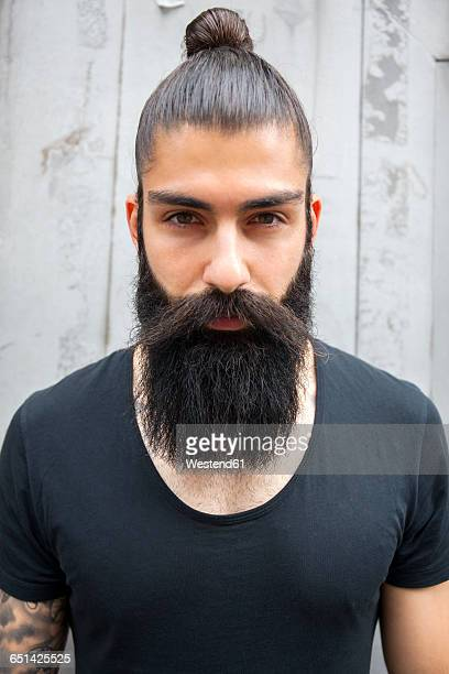 Portrait of young man with full beard and bun