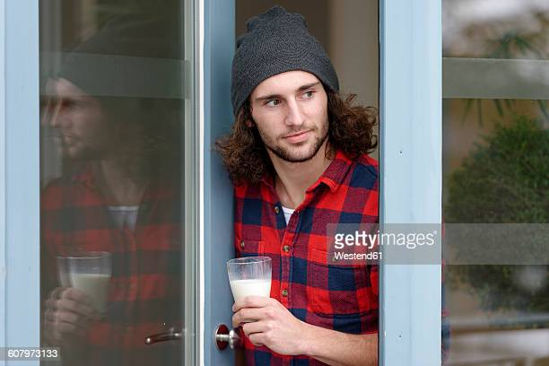 Portrait of young man with glass of milk