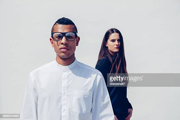Portrait of young man with glasses and woman behind him standing in front of white background