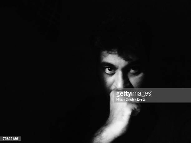 Portrait Of Young Man With Hand On Chin Against Black Background
