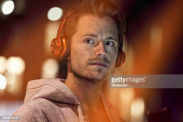 Portrait of young man with headphones listening music at night