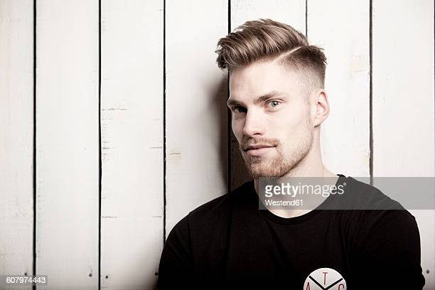 Portrait of young man with quiff in front of wooden wall