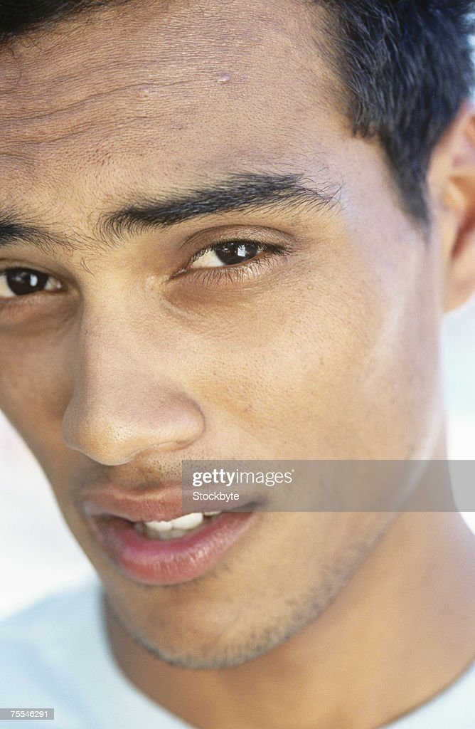 Portrait of young man with raised eyebrow,close-up : Stock Photo