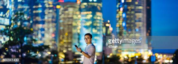 Portrait of young man with smartphone against skyline of downtown financial district of Hong Kong at night