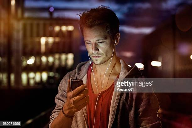 Portrait of young man with smartphone and earphones listening music at night