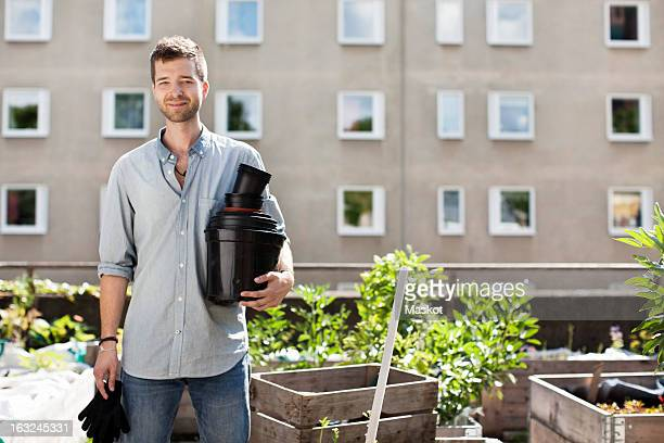Portrait of young man with stacked flower pots standing at urban garden
