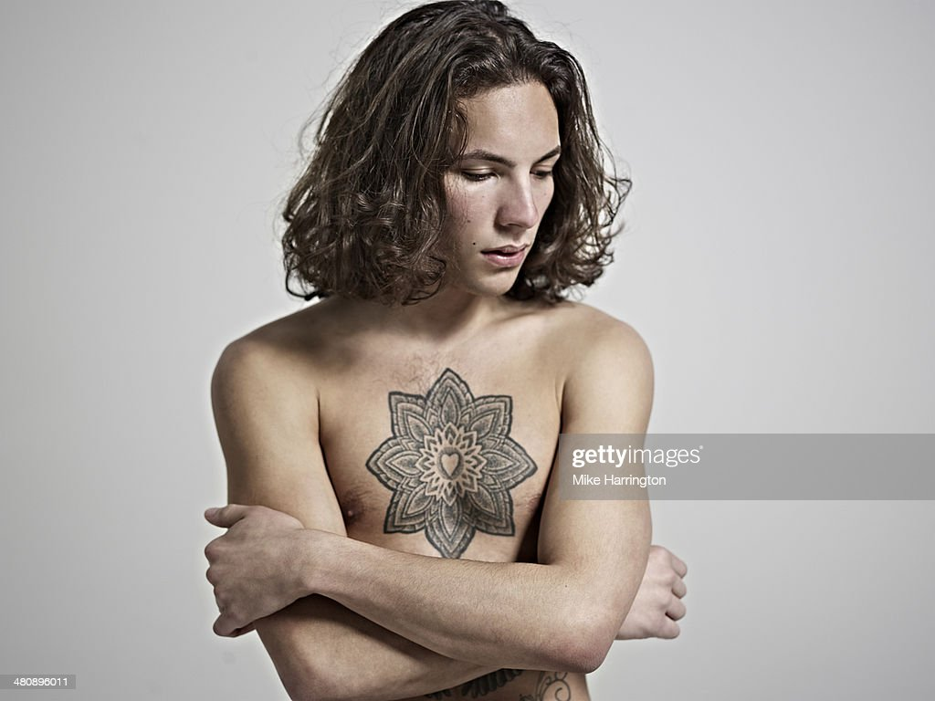 Portrait of young man with tattoo on his chest. : Stock Photo