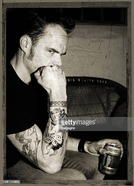 Portrait of Young Man with Tattoos Drinking Beer