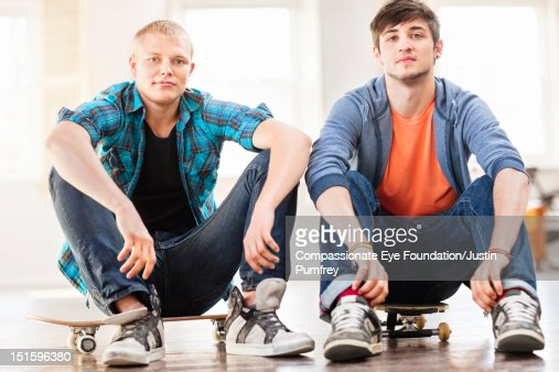 Portrait of young men sitting on skateboards : Photo