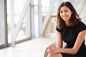 Portrait of young mixed race Asian businesswoman sitting