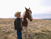 Authentic young cowgirl on range with horse in Big Timber, Montana
