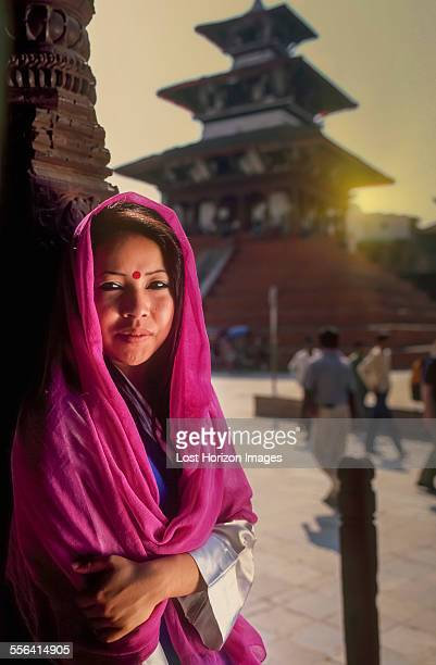Portrait of young Nepalese woman sitting outside temple, Kathmandu, Nepal