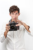 Portrait of young photographer with vintage camera gesturing against white background
