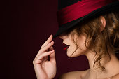 Portrait of young pretty woman with dark red lips wearing black hat with red band. Beauty studio shot.