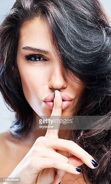 Portrait of young sexy woman with finger on lips.