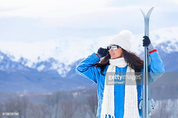 Portrait of young skier holding skis on top snow mountain