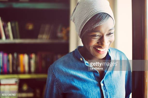 Portrait of young smiling African woman close to window