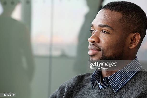 Portrait of young smiling businessman looking away