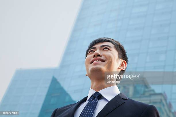Portrait of young smiling businessman outside glass building