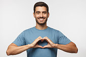 Portrait of young smiling man in blue t-shirt showing heart sign isolated on gray background