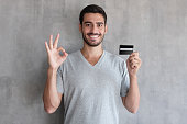 Portrait of young smiling man in t shirt, holding credit card and showing okay sign, standing against gray textured wall