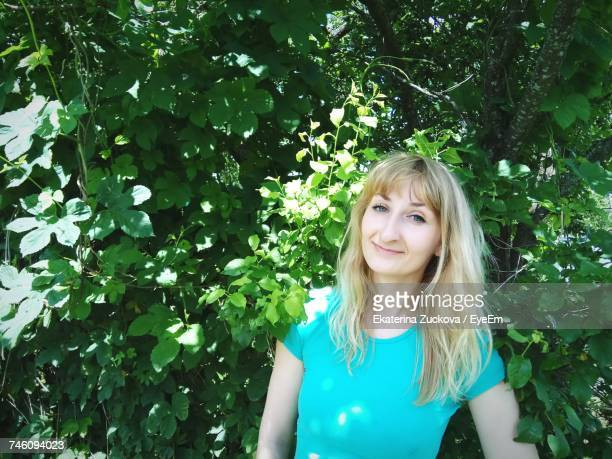 Portrait Of Young Smiling Woman Standing Against Plants