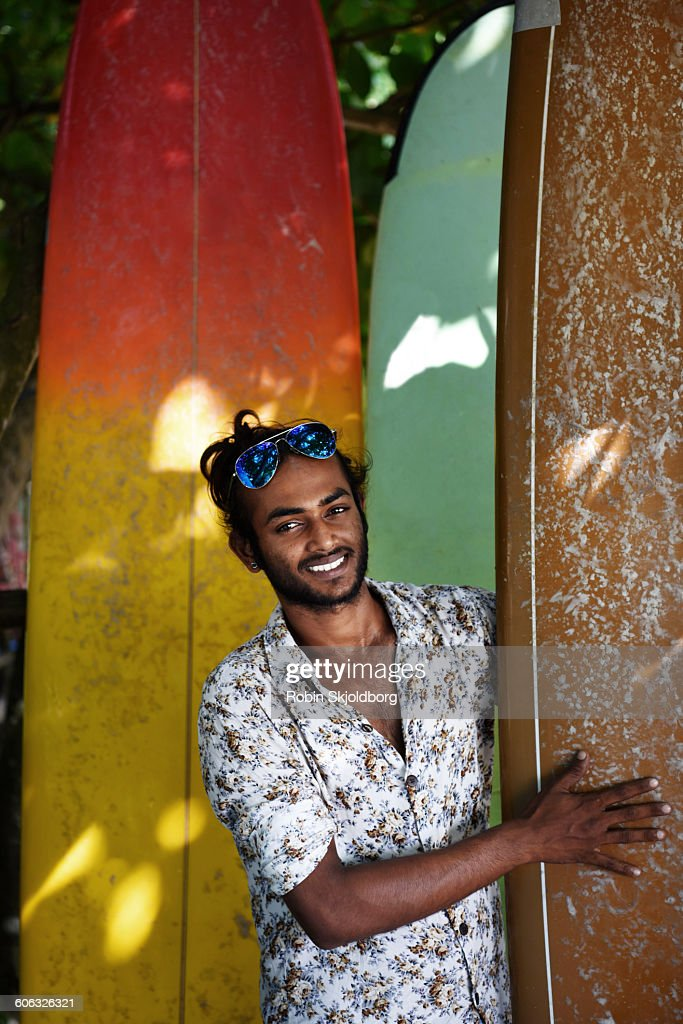 Portrait of young Sri Lankan Man with surfboards