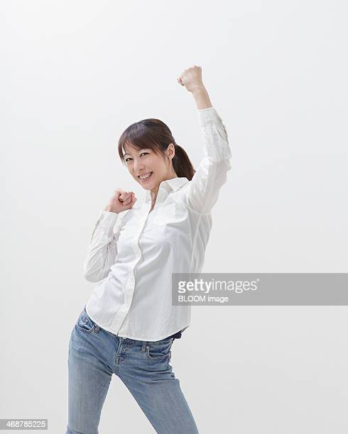 Portrait of young stylish woman punching the air