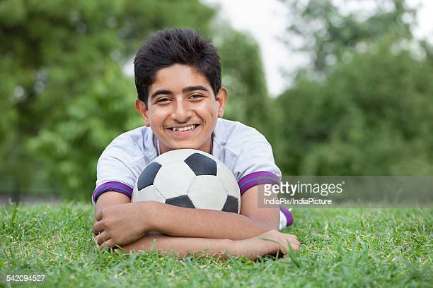 Portrait of young teenage boy with soccer ball lying on grass