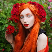 Portrait of young unusual pale girl with red hair in rose garden. Beautiful redhead woman with hairdo from roses. Pale skin. Expressive look