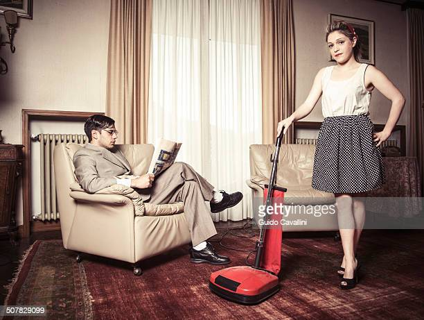 Portrait of young vintage couple in sitting room with vacuum cleaner