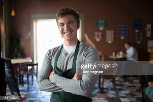 Portrait of young waiter in coffee house