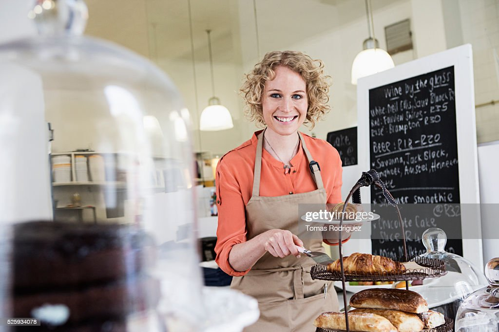 Portrait of young waitress holding plate with sweet buns : Foto de stock
