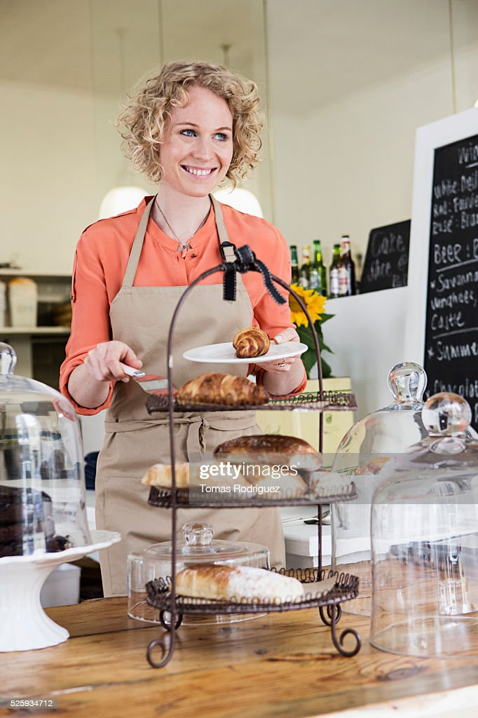 Portrait of young waitress holding plate with sweet buns : Stock Photo