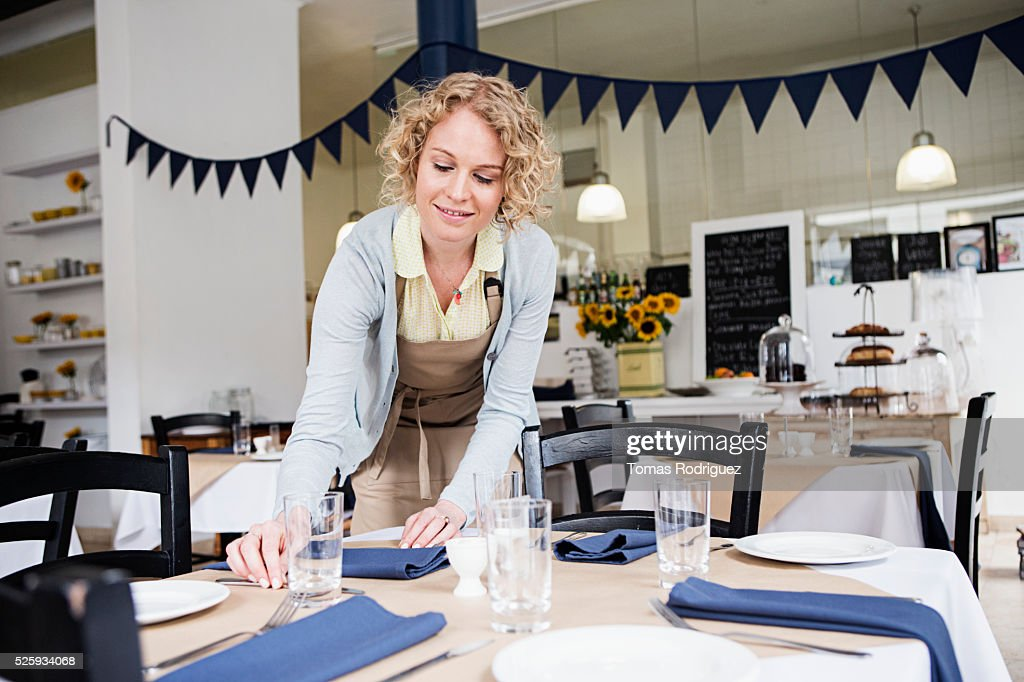 Portrait of young waitress setting table at restaurant : Stock Photo