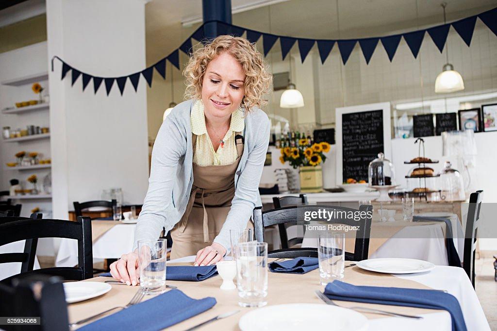 Portrait of young waitress setting table at restaurant : Foto de stock