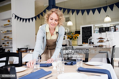 Portrait of young waitress setting table at restaurant : Stockfoto