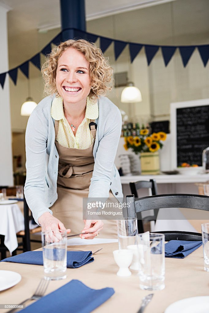 Portrait of young waitress setting table in restaurant : Stockfoto