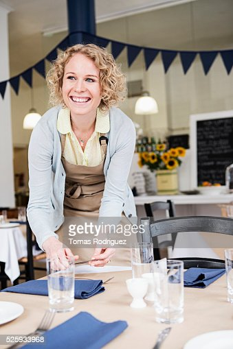 Portrait of young waitress setting table in restaurant : Stock Photo
