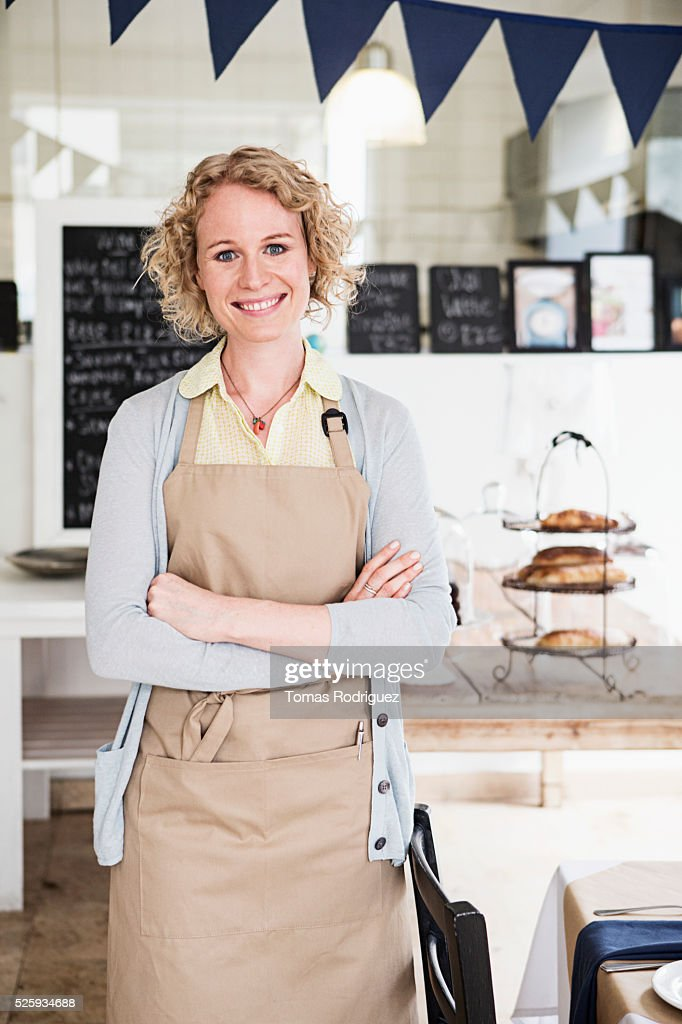 Portrait of young waitress standing in restaurant : Photo