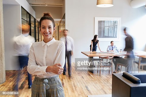 Portrait of young white woman in a busy modern workplace : Foto de stock