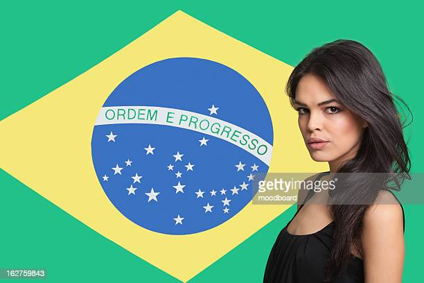 Portrait of young woman against Brazilian flag