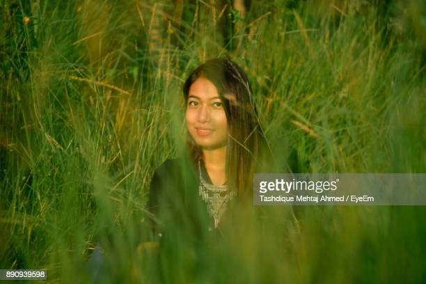 Portrait Of Young Woman Amidst Grass