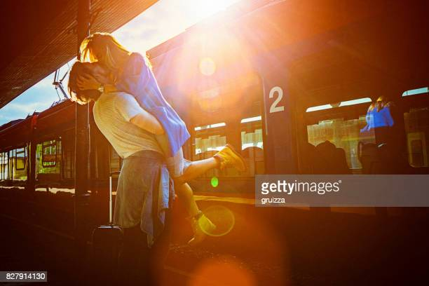 Portrait of young woman and man embracing at the railway platform