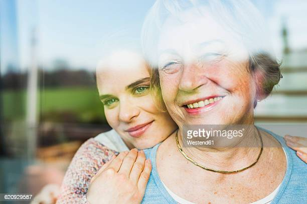 Portrait of young woman and senior woman behind windowpane