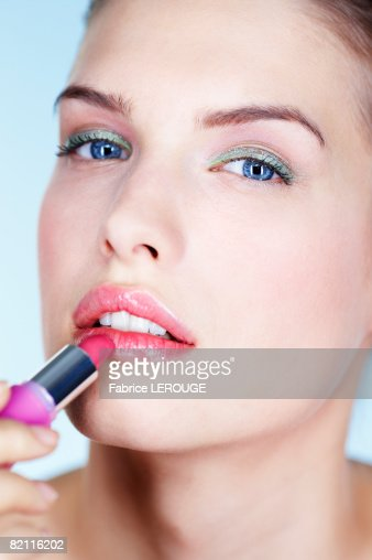 Portrait of young woman applying lipstick
