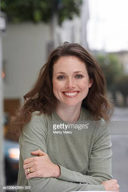 Portrait of young woman at cafe table, smile