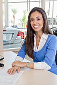 Portrait of young woman at car showroom